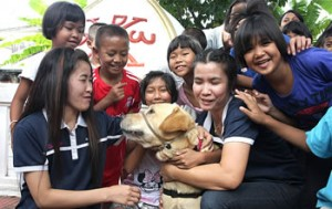 "Hawn and Booster have traveled all over the world to teach others about the healing power of dogs. Hawn said Booster has fostered international relations by serving as a ""social bridge"" in Cuba and comforting children with HIV in Thailand, where this photo was taken."